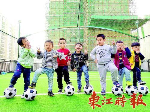 小朋友和足球在一起,萌哒哒的.