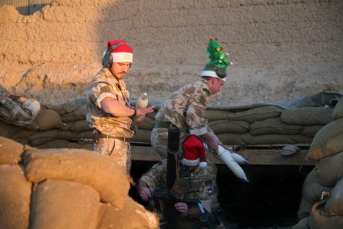 塔利班 英军 圣诞帽/这队驻阿英军士兵在落日中唱起圣歌。