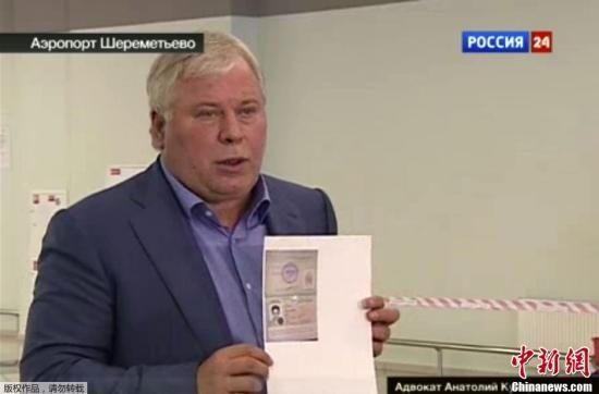 """据美联社报道,美国""""棱镜门""""项目泄密者爱德华·斯诺登获得有限期为一年的俄罗斯临时难民身份。图为俄罗斯律师库切列纳向媒体展示允许斯诺登进入俄罗斯境内临时文件的照片。"""