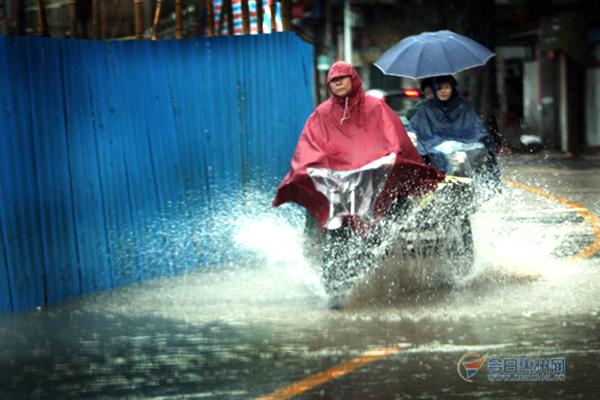 一辆摩托车在驶过积水处时溅起很大的水花.