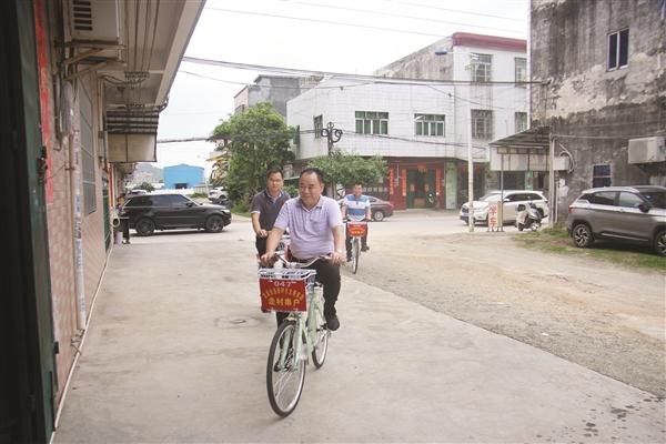 """宫庭村""""两委""""干部骑自行车去村民家中了解情况。"""