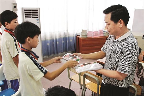 华红先(生前)为学生发毕业照。 兴汉小学政教处供图