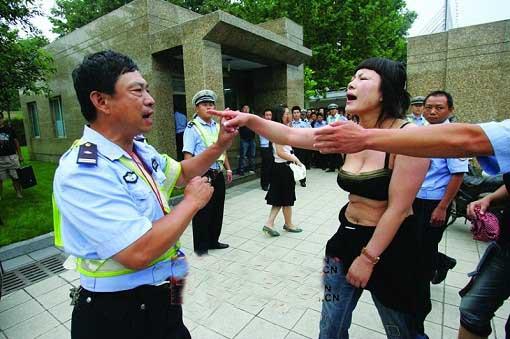 女子上身仅穿内衣 气势汹汹指着被打民警贾世良
