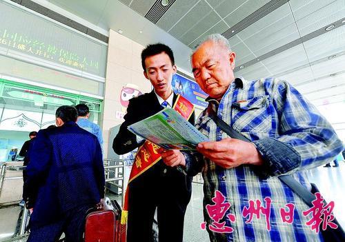 局银川客运段的工作人员向旅客分发新的列车时刻表